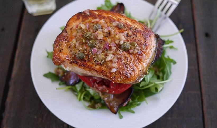 Ψητός σολομός με σάλτσα λεμονιού και κάππαρης πάνω σε σαλάτα με ντομάτα και καπνιστό μπέικον